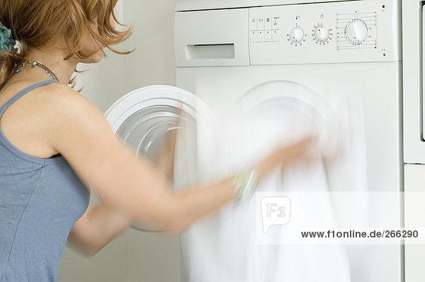 Frau entleert Waschmaschine