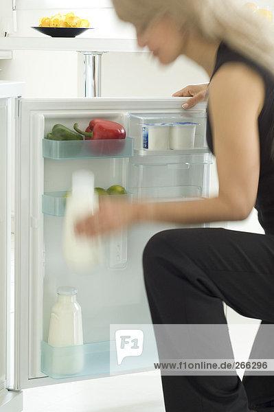 Frau sucht im Kühlschrank