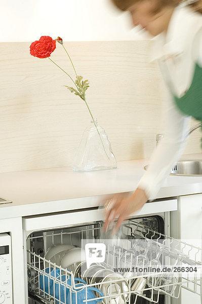 Frau beim Füllen der Geschirrspülmaschine