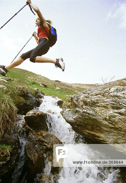 Frau springen über Mountain Stream auf Nordic-walking-tour