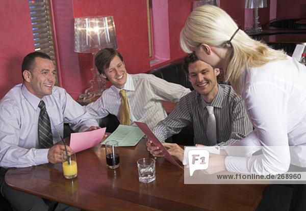 die Bestellungen von drei männliche Freunde sitzen im Restaurant Kellnerin