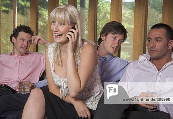 Gruppe Geschäftsleute sitzen zusammen mit Frau Gespräch auf ihrem Handy
