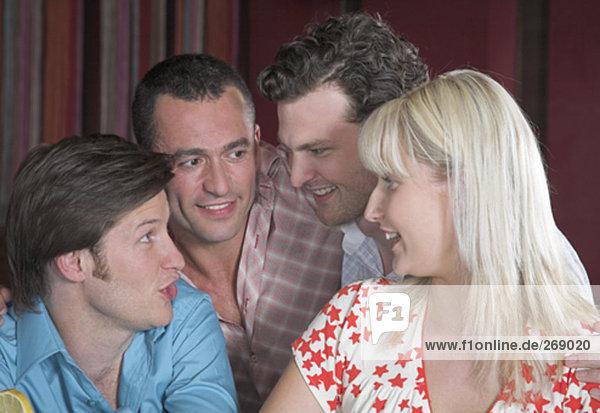 Gruppe von vier Freunden sprechen in Nachtclub