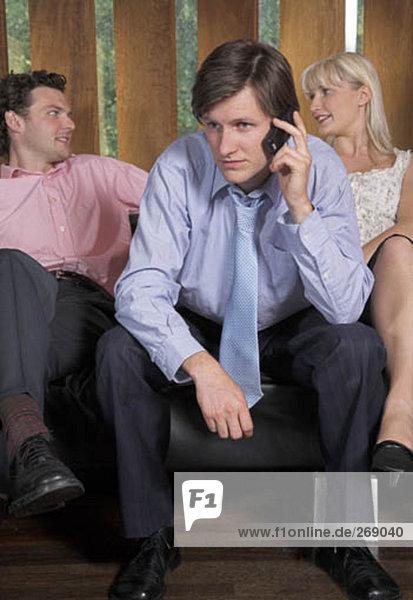 young Businessman haben ein Gespräch auf Handy  während seine Freunde sprechen