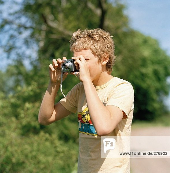 Boy photographing outdoors.