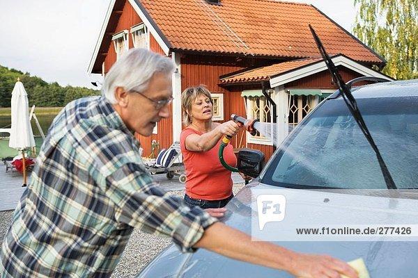 Außenaufnahme Frau Mann Wohnhaus Auto waschen