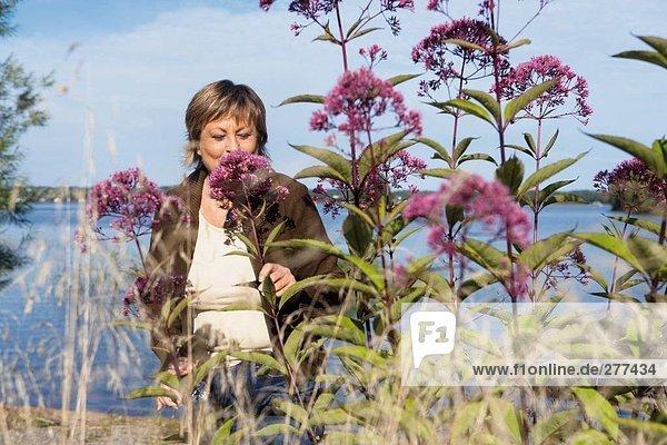 Eine Frau eine Blume riecht.
