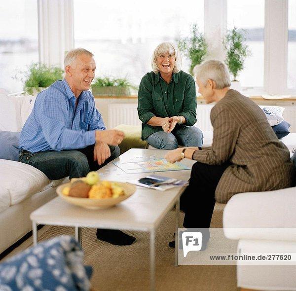 Drei Personen zusammen in einem Wohnzimmer.