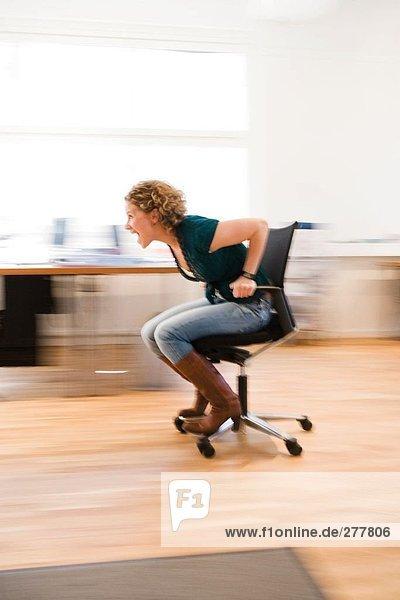 Eine Frau in voller Geschwindigkeit auf ein Bürostuhl.