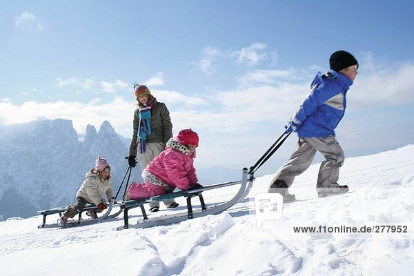 Woman with her three children on snow