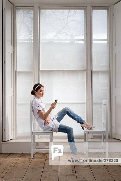 Frau auf Stühlen mit Handheld-Computer