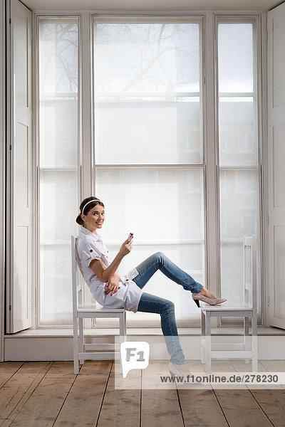 Frau auf Stuhl sitzend mit Handy