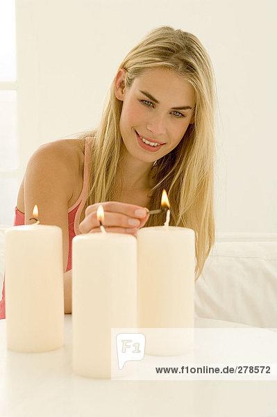 Frau zündet drei Kerzen an