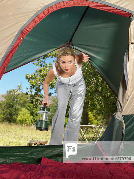 Junge Frau schaut ins Zelt