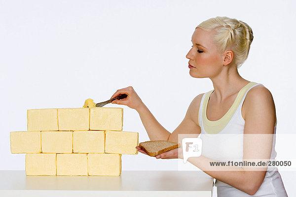 Junge Frau beim Butterkratzen