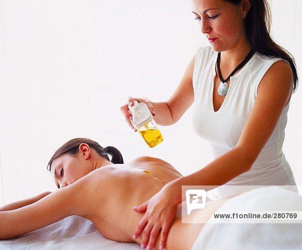 Rückansicht des jungen Frau immer wieder Massage von Massage-Therapeut