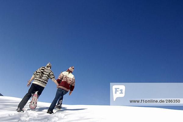 Junges Paar im Schnee  Rückansicht