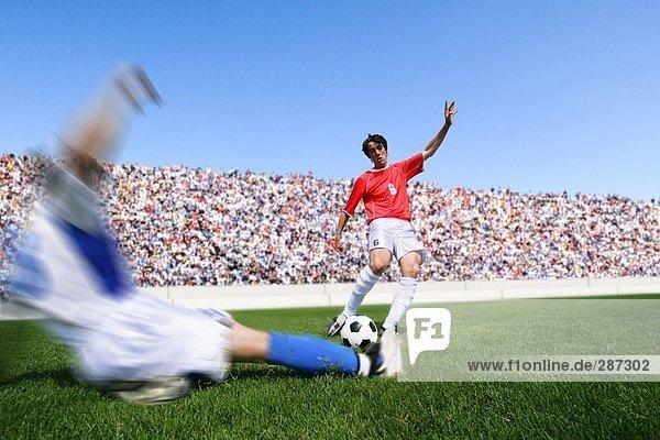 Fußball-Spieler treten Ball als Verteidiger Dias