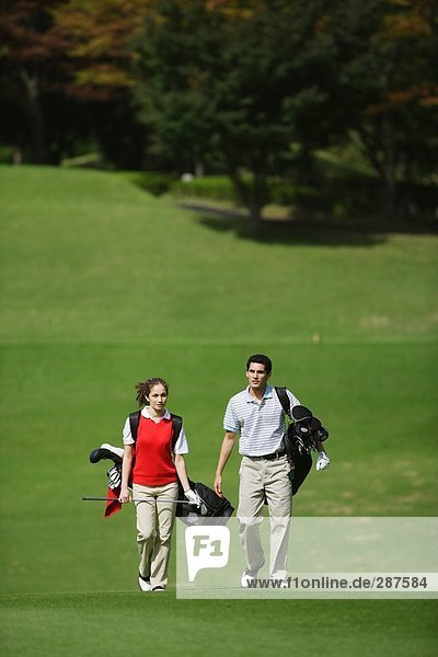 Frontansicht des ein paar Wandern auf dem Fairway  wie sie ihre Golfbeutel tragen