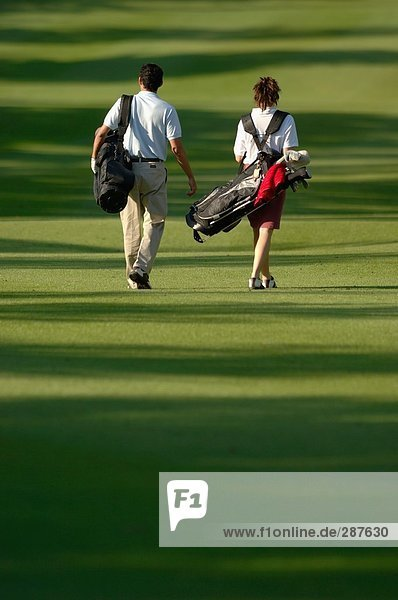 Rückansicht ein paar Walking auf dem Fairway  wie sie ihre Golfbeutel tragen