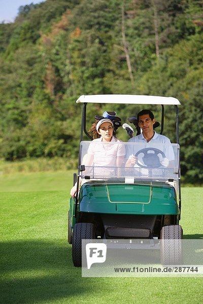 Vorderansicht eines Paares sitzen in einem Golf-cart