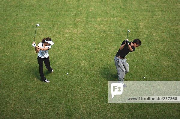 Mann und Frau spielen gleichzeitige Golfschlägen