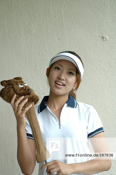 Woman holding a golf club with a cute cover