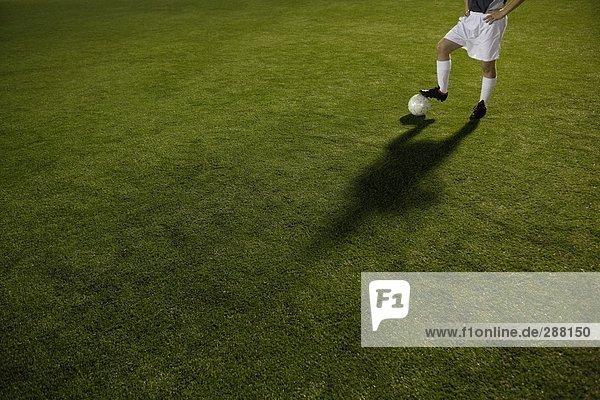 Fußball-Spieler und Ball im Feldanbau