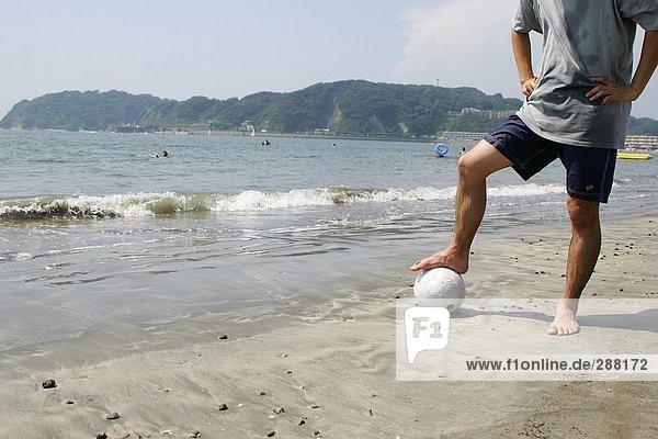 Junger Mann posiert mit einem Fußball am Strand