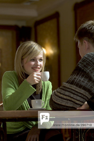 junge Frau im Cafe flirtet mit Mann sitzt