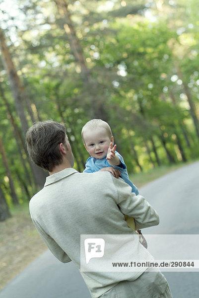 Rückansicht des Vaters haben einen Spaziergang durch den Wald mit seinem baby