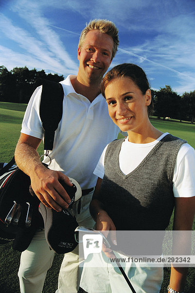 A man and a woman playing golf.