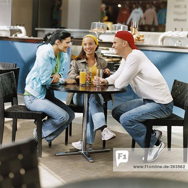 Drei Personen in einem Café.