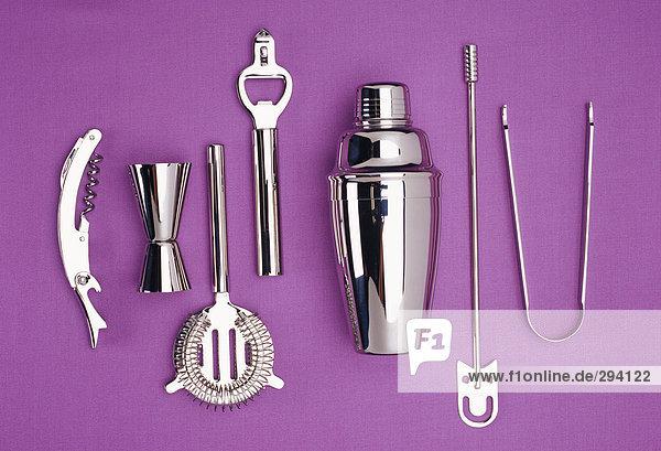 Küchenutensilien aus rostfreiem Stahl auf einem violetten Hintergrund. Küchenutensilien aus rostfreiem Stahl auf einem violetten Hintergrund.