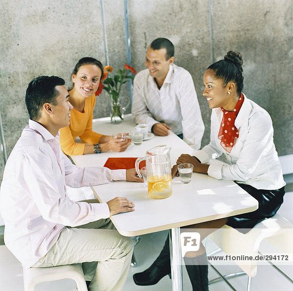 Zwei Männer und zwei Frauen sitzen von einer Tabelle mit Erfrischungen.