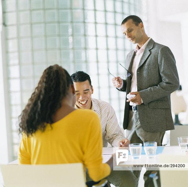 Drei Menschen arbeiten von einer Tabelle.