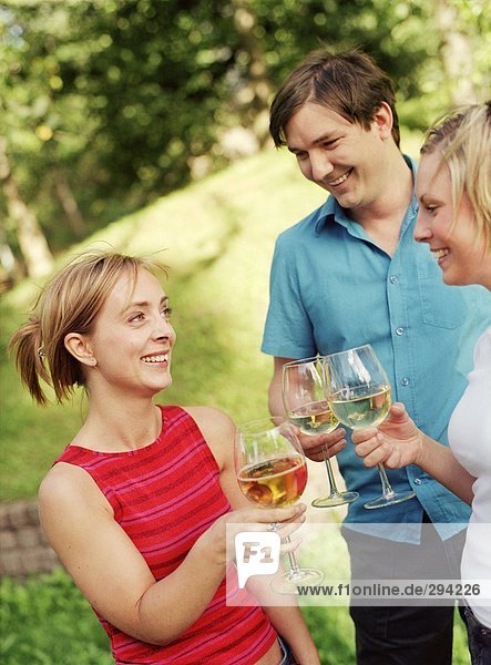 Three people toasting in a garden.