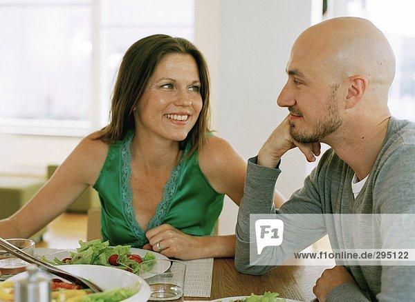 Ein Mann und eine Frau an einem Küchentisch.