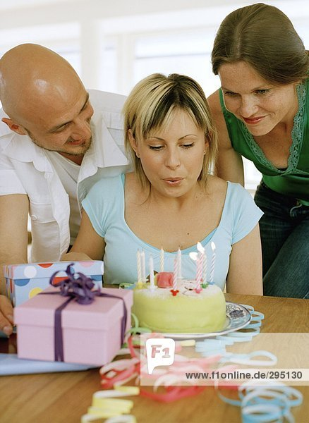A woman blowing out candles on a birthday cake.