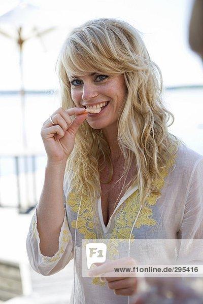 Einer blonden Frau kaute auf einen Snack.