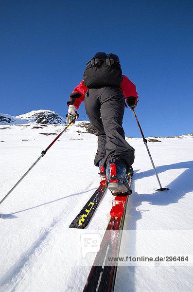 Ein Skifahrer auf dem Weg bis auf eine Ski-Slope Rückansicht.