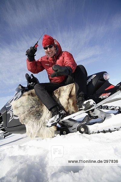 Ein Mann von einem Snowcat jigging.