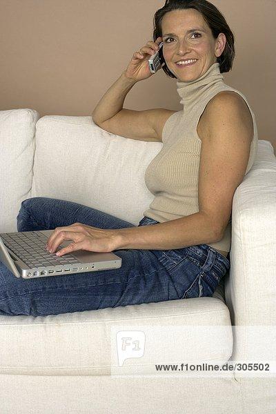 Frau sitzt mit einem Laptop auf einem Sofa und telefoniert mit einem Handy  fully_released
