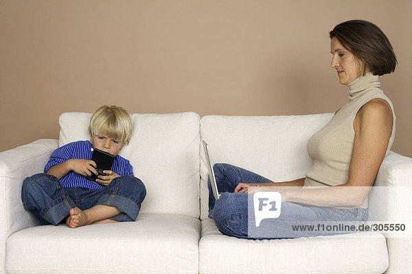 Mutter und Sohn sitzen auf einem Sofa  Frau arbeitet am Laptop  Junge spielt mit Minicomputer  fully_released
