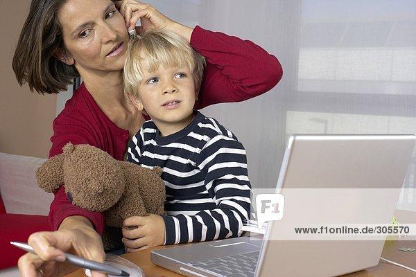 Mutter telefoniert mit dem Handy und macht sich Notizen  Sohn sitzt mit Teddybär auf ihrem Schoss  fully_released