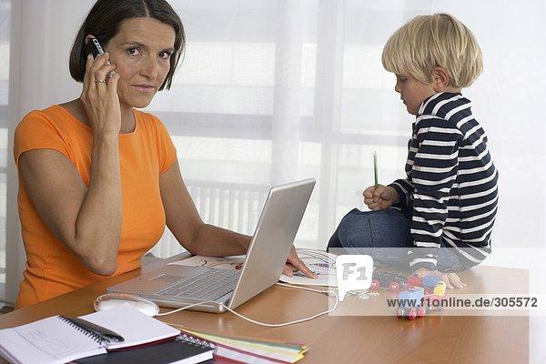 Mutter telefoniert mit einem Handy  Sohn sitzt auf dem Tisch und malt  fully_released