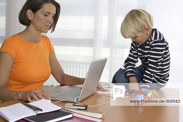 Mutter arbeitet am Laptop  Junge sitzt auf dem Tisch und spielt  fully_released
