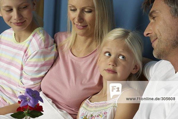 Eltern sitzen neben ihren zwei blonden Töchtern - Familie - Harmonie  fully_released