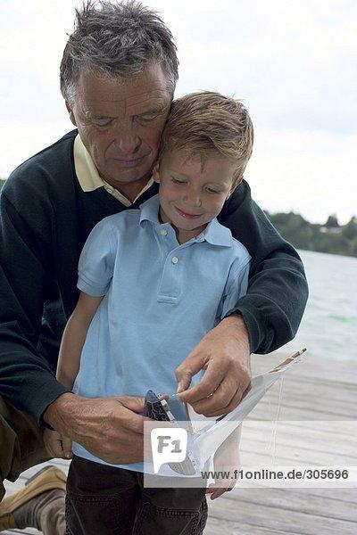 Grauhaariger Mann mit einem Jungen vor sich repariert ein Spielzeugboot - Freizeit - See - Familie  fully_released