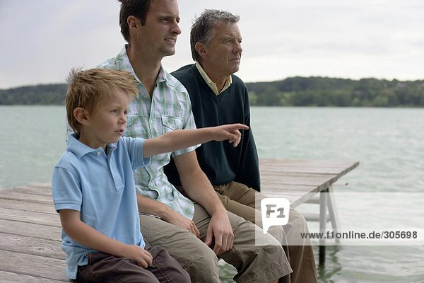 Boy  father and grandfather sitting on a wooden footbridge at a lake